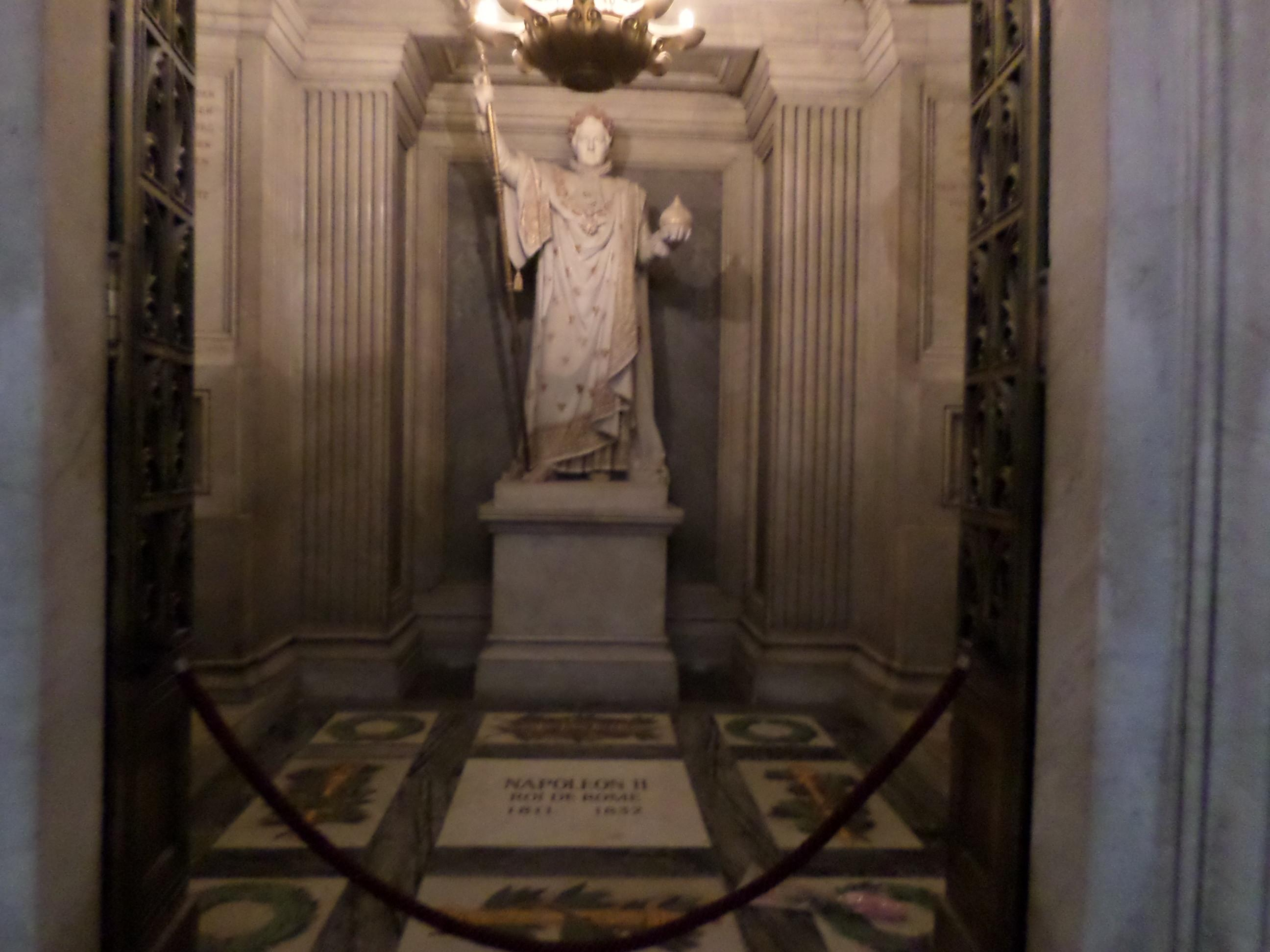 A statue of Napoleon inside his tomb declaring him the King of Rome. The tomb is within wa