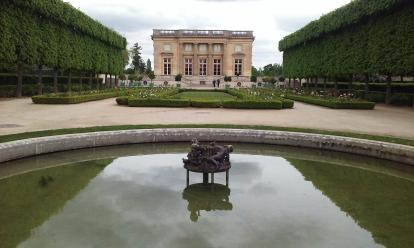 Le Petit Trianon at Versailles. A beautiful symmetric garden with a pond. The gardens of V