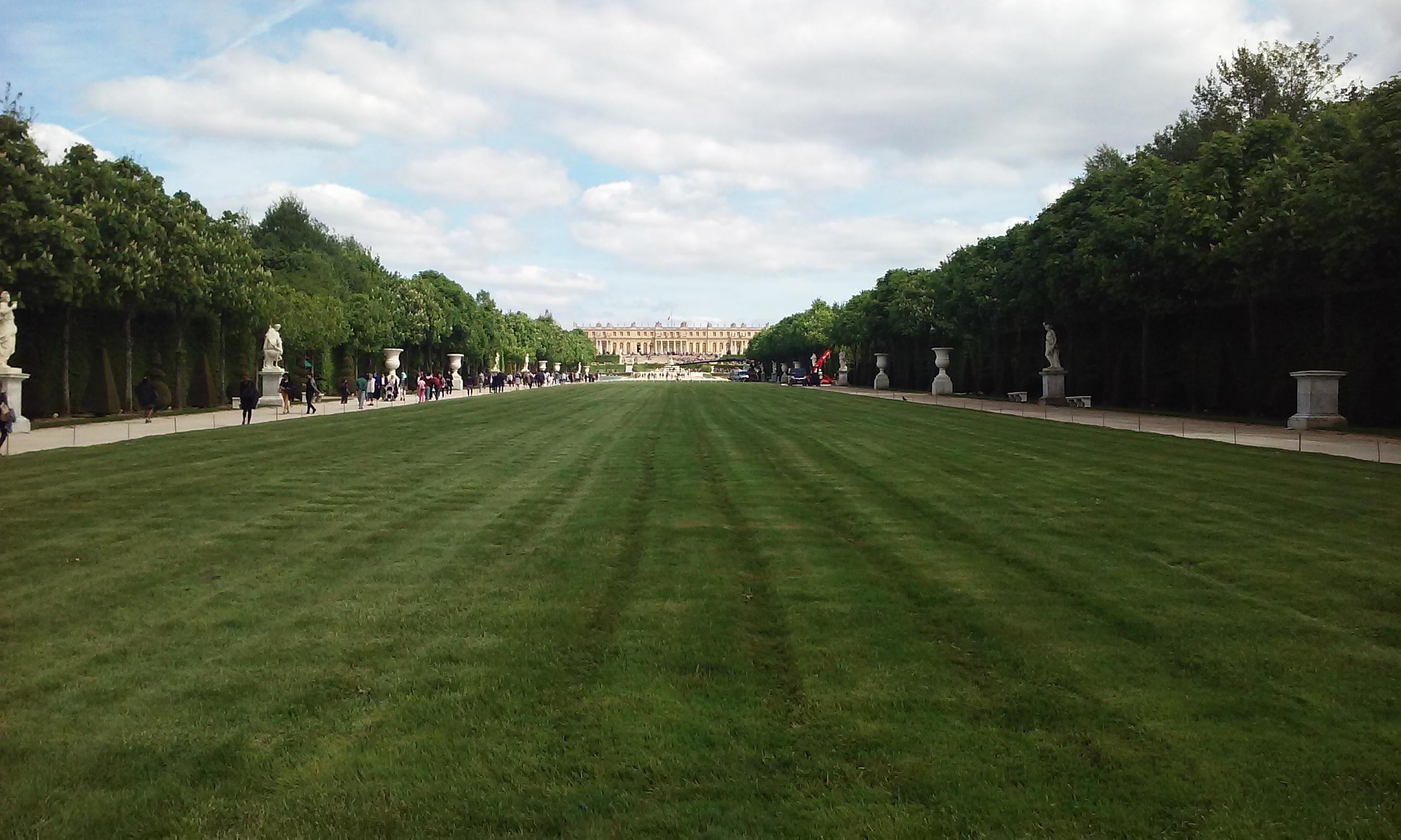 A long grass lawn leading to the Palace of Versailles. Beyond this lawn is the Grand Canal
